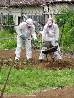 Workers in radiation suits shovel dirt in Iitate, Fukushima Prefecture, on June 6, 2012. (Photo by Bunyou Ishikawa)
