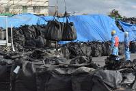 汚染土などが詰め込まれたフレコンバッグをクレーンを使い保管場に積み上げる作業員ら=福島県大熊町で2016年2月24日午後3時、金志尚撮影
