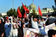 「我々は神以外には従わない」などと叫び、反政府デモを行うシーア派住民。隣国サウジアラビアで1月に処刑された同派指導者ニムル師の肖像画を手にしている=バーレーン東部シトラ島で2016年2月5日、田中龍士撮影