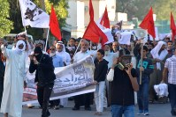 反政府デモを行うシーア派住民の傍らで、防護マスクをかぶる青年。治安部隊による催涙ガスを警戒している=バーレーン東部シトラ島で2016年2月5日、田中龍士撮影