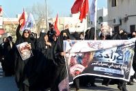 「神は彼らに復讐する」などと叫び、反政府デモを行うシーア派住民の女性たち。隣国サウジアラビアで1月に処刑された同派指導者ニムル師の肖像画を手にしている=バーレーン東部シトラ島で2016年2月5日、田中龍士撮影
