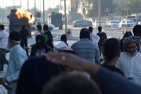 デモ隊が投げた火炎瓶ビンで燃え上がる治安部隊の装甲車が迫り、逃げ惑うデモ参加者=バーレーン東部シトラ島で2016年2月5日、田中龍士撮影