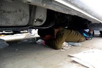 治安部隊が放つ催涙弾の発砲音に震え、自動車の下に身を隠す少年。静かになった後、近く置いていた牛乳を手に逃げた=バーレーン東部シトラ島で2016年2月5日、田中龍士撮影