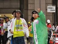 ゴールしたランナーを案内する小村純子さん(右)=東京都江東区の東京ビッグサイトで2016年2月28日、飯山太郎撮影