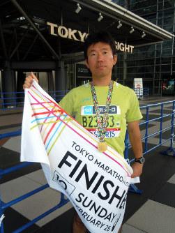 完走記念のメダルをかけ、タオルを持つ葛西記者