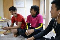漁を終え、宿舎で談笑するイブさん(左)とルスさん(中央)ら=鳥取県岩美町で、高嶋将之撮影