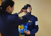 女性警察官の手助けを受け、制服を試着する学生(右)=県庁で