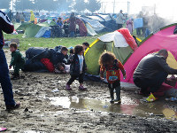 Children walk in the mud amidst tents at a refugee camp in the outskirts of Idomeni in northern Greece, on March 1, 2016. (Mainichi)