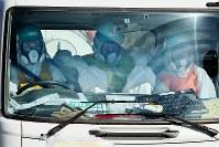 防護服を着て構内を通行するトラックに乗る作業員ら=福島第1原発で2015年11月6日、森田剛史撮影(一部画像を加工しています)
