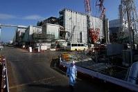 爆発事故の爪痕が残るなか、廃炉作業が進む3号機の原子炉建屋(奥中央)。右奥は4号機=福島第1原発で2016年2月23日、森田剛史撮影