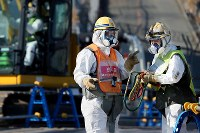 空間放射線量が高い凍土遮水壁の建設現場で、放射線を遮る効果のある金属が含まれたベストを着て作業する労働者ら(一部画像を加工しています)=福島第1原発で2016年2月23日、森田剛史撮影