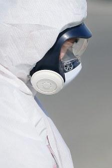 全面マスクと防護服を着用し、入退域管理施設を出て放射線量が高い現場に向かう作業員の男性=福島第1原発で2016年2月12日、森田剛史撮影