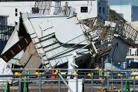 いまだに倒壊した建屋が残る海側遮水壁付近の構内を歩く作業員=福島第1原発で2015年11月6日、森田剛史撮影