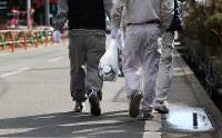 ビニール袋にマスクを入れ、入退域管理施設に向かう作業員。構内でも一部、防護服を着ずに歩ける場所もある=福島第1原発で2016年1月25日、小川昌宏撮影