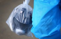 ビニール袋にマスクを入れ、入退域管理施設に向かう作業員=福島第1原発で2016年1月25日、小川昌宏撮影
