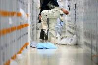ロッカーが並ぶ入退域管理施設の更衣スペースで靴下を二重にはく作業員の男性。手袋は三重だ=福島第1原発で2016年2月12日、森田剛史撮影