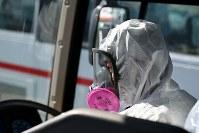 防護服を着て構内を回るバスを運転する作業員の男性=福島第1原発で2015年11月6日、森田剛史撮影