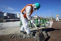 海側遮水壁の近くで小石をかき集める作業員=福島第1原発で2016年2月23日、森田剛史撮影