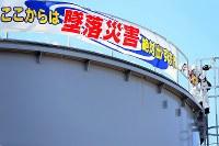 現場での事故防止を呼びかける横断幕が掲げられた汚染水のタンクに登る作業員=福島第1原発で2016年2月12日、森田剛史撮影