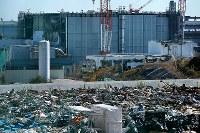 事故の爪痕が残る3号機の建屋。手前は構内の作業で出た放射能に汚染された廃棄物の仮置き場=福島第1原発で2015年11月5日、森田剛史撮影