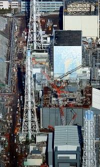 放射線量が高い原子炉建屋周辺。奥から手前に向かって1~4号機まで並ぶ=福島第1原発で2015年11月27日、本社ヘリから森田剛史撮影