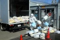 防護服などの廃棄物を車に積み込む作業員ら=福島第1原発で2016年2月23日、森田剛史撮影
