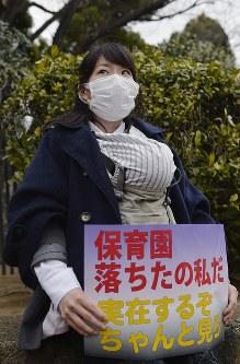 赤ちゃんを胸に「保育園落ちたの私だ」と書かれたプラカードを持って国会前に座り込む女性=東京都千代田区で2016年3月5日午後3時16分、猪飼健史撮影