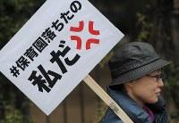 国会前で「保育園落ちたの私だ」と書かれたプラカードを持つ女性=東京都千代田区で2016年3月5日午後3時2分、猪飼健史撮影