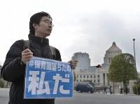「保育園落ちたの私だ」と書かれたプラカードを持って国会前に立つ人=東京都千代田区で2016年3月5日午後2時44分、猪飼健史撮影