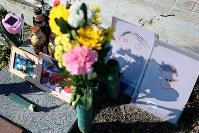 「ほら、子供たちが描いた絵だぞ」。月命日に津波で長男健一さん(当時41歳)が行方不明になった郵便局跡地に花を供える佐藤一夫さん(74)は、孫たちが父の日に描いた似顔絵を祭壇に添えた。震災当時1歳だった健一さんの長男孝郁(たかふみ)君(6)は、あの日の朝、出勤するお父さんに弁当を手渡し、「バイバイ」と手を振ったのが最後の別れになった=福島県浪江町で2015年11月11日、森田剛史撮影