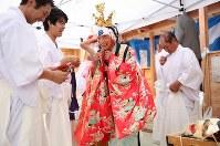 震災で全壊した葉山神社がようやく再建され、千葉文彦さん(65)=中央=は、仲間たちと雄勝法印神楽を奉納した。千葉さんは、まだ見つからない妻真紀子さん(当時56歳)が作ってくれた鮮やかな衣装に身を包んだ。千葉さんが幼少期から遊び、現在は総代も務める神社の再建を祝う特別な神楽。「せっかくだからおっかあのを着っか」と真紀子さんが作ってくれた衣装を意識して袖を通した。千葉さんは「骨とか見つかってくれるに越したことはない。でも成仏してくれたかの方が大事だと思ってんだ」=宮城県石巻市で2015年9月20日、小川昌宏撮影