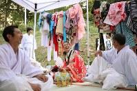 仲間たちと雄勝法印神楽を奉納した千葉文彦さん(65)=中央=。千葉さんは、まだ見つからない妻真紀子さん(当時56歳)が作ってくれた衣装を着た。普段は神楽の衣装は仲間と共有し、形見の衣装も「みんなで来てもらった方がいい」。それでも、特別な神楽だから「せっかくだからおっかあのを着っか」と真紀子さんが作ってくれた衣装を意識して袖を通した。千葉さんは「骨とか見つかってくれるに越したことはない。でも成仏してくれたかの方が大事だと思ってんだ」と言う。それでも自宅には真紀子さんの洋服がハンガーに掛けられたままだ。「やっばり捨てたりはかわいそうでできないね」=宮城県石巻市で2015年9月20日、小川昌宏撮影