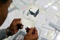福島県富岡町民を避難誘導中、津波にのまれ行方不明になった双葉警察署の警察官、佐藤雄太さん(当時24歳)。現在は震災遺産として町内の公園に展示されている大破したパトカーの前にはポストが設置され、地域住民や全国の警察官から寄せられた手紙や名刺はこれまでに1000通以上になる。中には「あの日 富岡駅前で守られた命を大切に生きています」と書かれたメッセージもあるが、震災から年を経るにつれ、その数も減ってきたことに、父の安博さん(57)は「風化が進んできていることを感じる」=福島市で2015年12月14日、森田剛史撮影