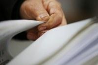 集まった1人1人の署名に目を落とす吉田税さん(81)。署名の束をめくる農家の吉田さんの手には、洗っても落ちない土がついている=岩手県陸前高田市で2016年2月17日、小川昌宏撮影