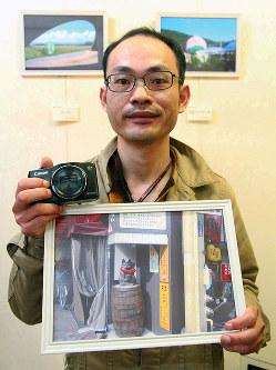 JR岡山駅前で撮影した作品と愛用のデジタルカメラを手にする北野和海さん=岡山市北区表町1で、瀬谷健介撮影