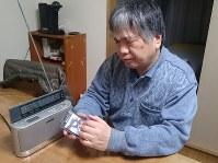 情報収集のため、据え置き型ラジオとスマートフォンを愛用する織田洋さん=東京都豊島区で、鈴木敦子撮影