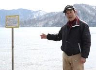 「魚の放射線量をより下げるために検証すべき時期だ」と決意を新たにする中禅寺湖漁協の鹿間久雄専務理事。釣った魚を持ち帰らないように促す看板(左)が立てられている=日光市中宮祠の中禅寺湖で
