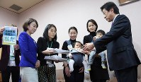 「保育園落ちた日本死ね!!!」ブログ賛同者の署名を受け取る塩崎恭久厚労相。左から2人目は民主党の山尾志桜里衆院議員=国会内で2016年3月9日午後2時42分、藤井太郎撮影