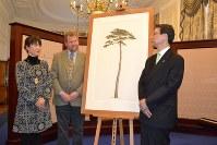 在英日本大使館に展示される「奇跡の一本松」の植物画を前に談笑する山中麻須美さんら=ロンドン市内の在英日本大使館で3月8日、坂井隆之撮影