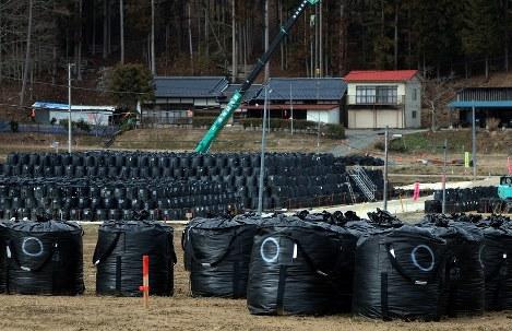民家前のかつての農地に積み上げられた、汚染土などを詰めたフレコンバッグ=福島県飯舘村で2016年3月10日午後、佐藤賢二郎撮影