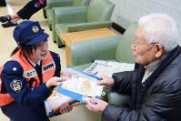 特殊詐欺への注意を呼び掛ける印刷物を配る徳島東署員(左)=徳島市中洲町1の中洲八木病院で、河村諒撮影