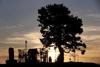 早朝から多くの人が訪れた日和山に昇る朝日=宮城県名取市閖上で2016年3月11日午前6時18分、森田剛史撮影