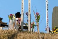 日和山に献花して手を合わせ、目頭を覆う女性=宮城県名取市で2016年3月11日午前6時56分、森田剛史撮影