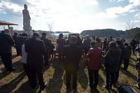 海の見える高台の慰霊碑前で手を合わせる遺族たち=宮城県南三陸町で2016年3月11日午前9時16分、喜屋武真之介撮影
