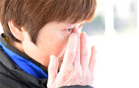 卒業式前に慰霊碑を訪れた福島県相馬市立磯部中学校の教諭、堀川智秋さん(54)。教え子の森谷友加里さん、宮崎朱里さん、弟の雅人さん、原田茉欧さん、稲山瑞紀さん、蛯原優斗さんを亡くした。東日本大震災発生当日も卒業式で、生徒を見送った後に被災。「磯部地区は5年経っても復興が進まないが、みんなには天国から見守っていてほしい」と話し、涙を流した=同市で2016年3月11日午前7時9分、山崎一輝撮影