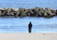 壊滅的な被害を受けた荒浜地区を訪れた男性は、花束を手にずっと海を見つめていた=仙台市若林区で2016年3月11日午後2時、佐々木順一撮影
