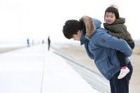 東日本大震災の地震発生時刻に防潮堤の上で黙とうする人たち=仙台市若林区で2016年3月11日午後2時46分、佐々木順一撮影