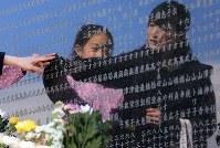 大川地区の慰霊碑に刻まれた友人の名前をなでる佐藤淳子さん(右)と菜那ちゃん親子=宮城県石巻市で2016年3月11日午後0時43分、梅村直承撮影