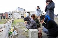大川小学校の校庭で亡くなった狩野蓮斗君のために花を供え祈りを捧げる遺族=宮城県石巻市で2016年3月11日午後2時12分、梅村直承撮影