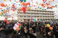 被災した荒浜小学校の前で風船を飛ばす人たち=仙台市若林区で2016年3月11日午後3時21分、佐々木順一撮影